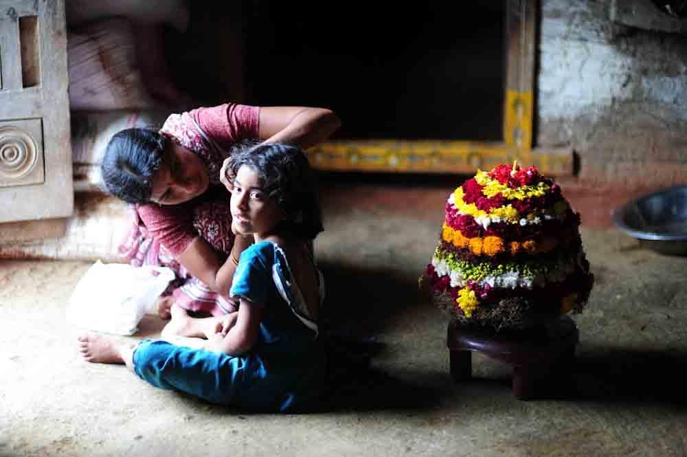 mother grooming daughter for Bathukamma Celebrations