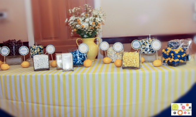 Yellow and blue wedding candy buffet with DIY signs anchored in lemons.