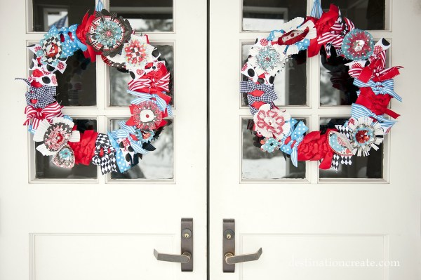 Handcrafted cupcake liner flower wreaths grace the wedding entrance.