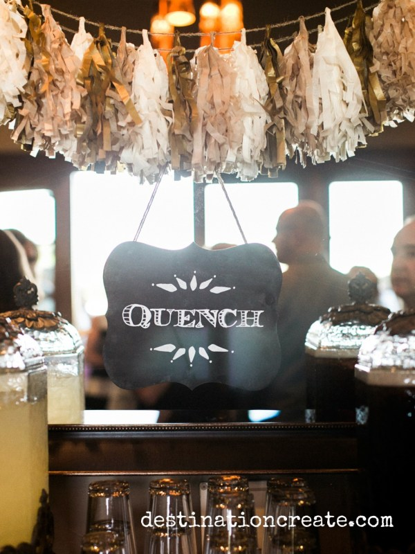 """Entice wedding guests to the bar with this fun chalkboard """"Quench"""" sign hung from a tissue paper tassel garland."""