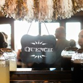 "Entice wedding guests to the bar with this fun chalkboard ""Quench"" sign hung from a tissue paper tassel garland."