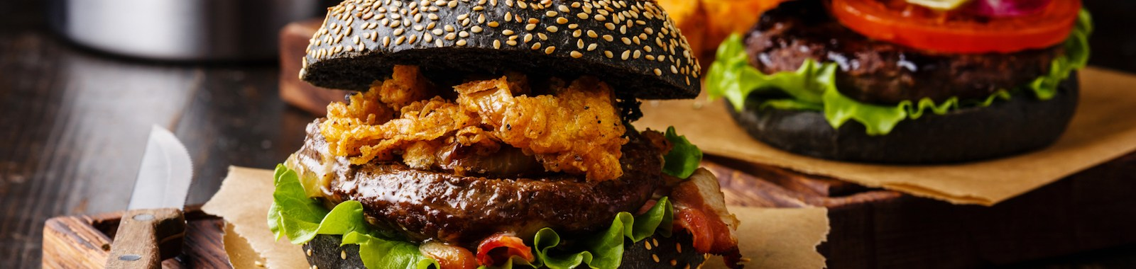Black burger with meat, onion rings and potato wedges