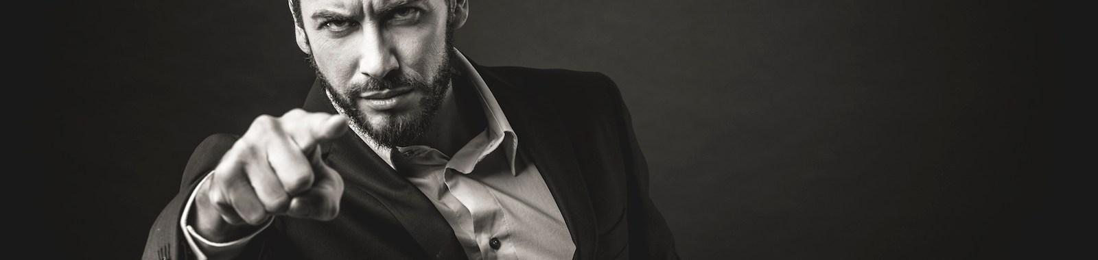 Aggressive businessman pointing finger against dark background