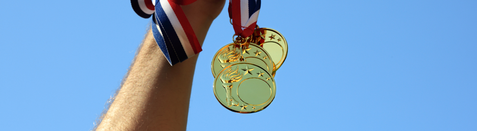 Winning at olympic games, hand holding gold medals