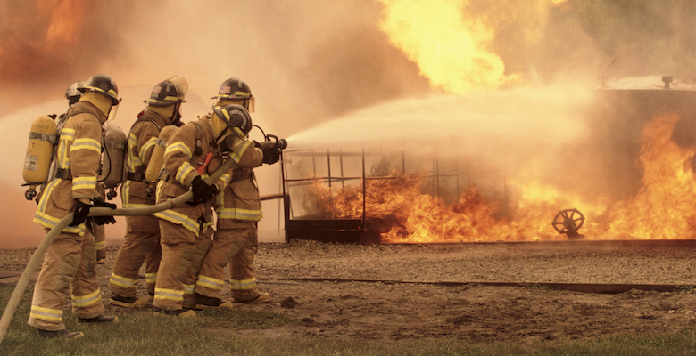 Side profile of a group of firefighters holding water hoses