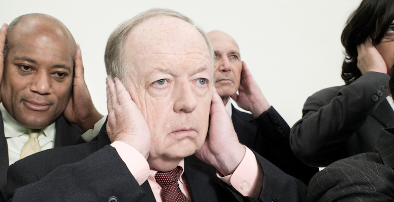 Businessmen covering ears
