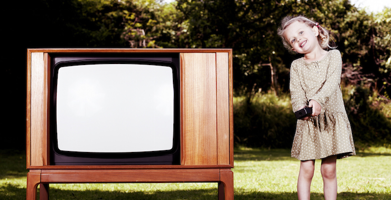 A young child standing in the garden, next to a 1970's television set.