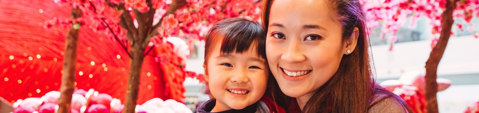 Pretty young mom cuddling lovely little daughter while both smiling joyfully at the camera in front of Chinese new year decorations