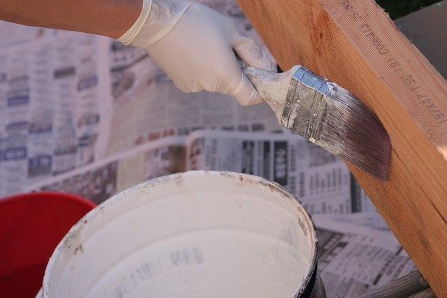 a general contractor wearing white gloves painting a large wooden plank