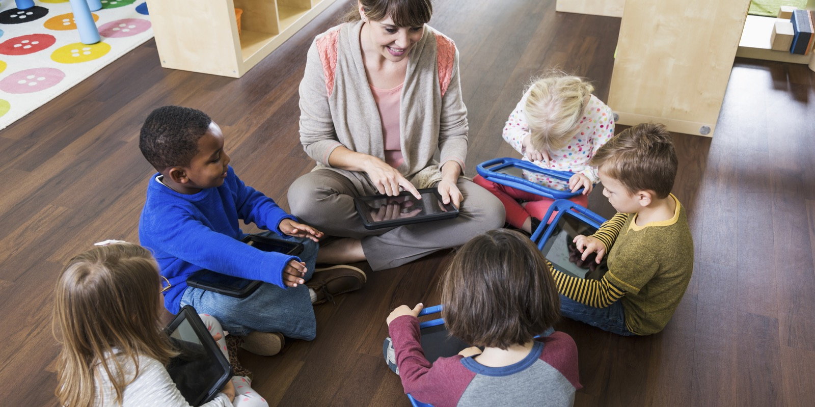 A multi-ethnic group of children and a female teacher sitting on the floor in a circle, in a preschool classroom using digital tablets.  They each have their own device on their lap.