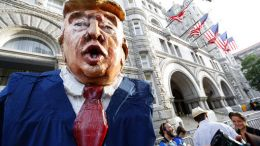 A protester wears a large likeness of President Donald Trump outside the Trump Hotel, Wednesday, June 28, 2017, in Washington. President Donald Trump is attending a fundraiser at the hotel. (AP Photo/Alex Brandon)