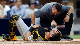 Pittsburgh Pirates catcher Francisco Cervelli (bottom) gets help from a trainer after a foul ball by San Diego Padres' Cory Spangenberg struck him in the fourth inning of a baseball game in San Diego, Saturday, July 29, 2017.  (AP)