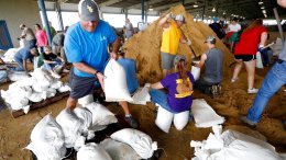 A volunteer loads sand bags on a pallet as others fill them for resident distribution, Tuesday, Aug. 29, 2017, at the Burton Coliseum in Lake Charles, La. (AP)