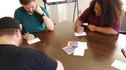 Clarion University students Seth Updegraff, Edward Green and Shayla Barrett write uplifting messages on #DearYoungPerson postcards. (Submitted photo)