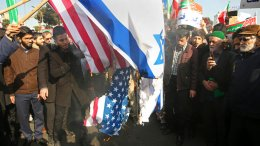 In this photo provided by Tasnim News Agency, Iranian demonstrators burn representations of U.S. and Israeli flags in a pro-government rally in the northeastern city of Mashhad, Iran, Thursday, Jan. 4, 2018. (AP)