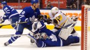 Pittsburgh Penguins center Derick Brassard (19) crashes into Toronto Maple Leafs goaltender Frederik Andersen (31) and is shoved out of the crease by defenseman Connor Carrick (8) during the third period of an NHL hockey game Saturday, March 10, 2018, in Toronto. (AP)