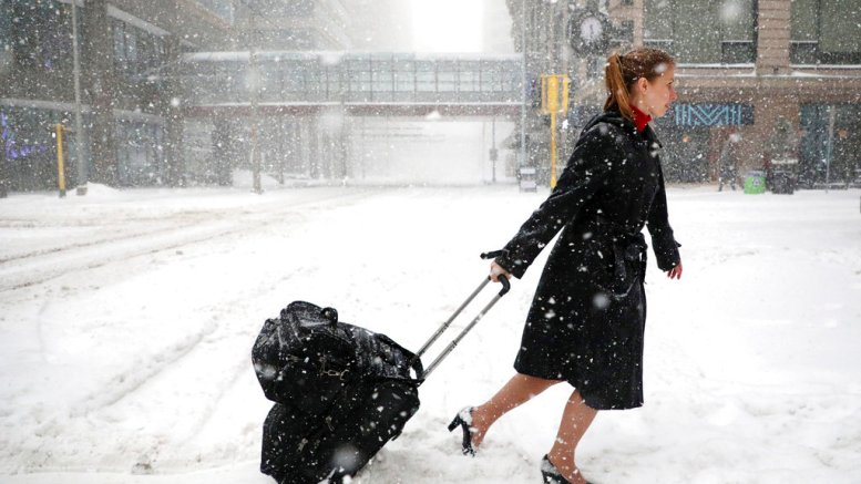 Delta Airlines flight attendant Victoria Flees trudges through the snow with her bags in downtown Minneapolis on the way back home from the light rail station after her flight to Paris was grounded along with all other planes at MSP because of weather, Saturday, April 14, 2018. (AP)