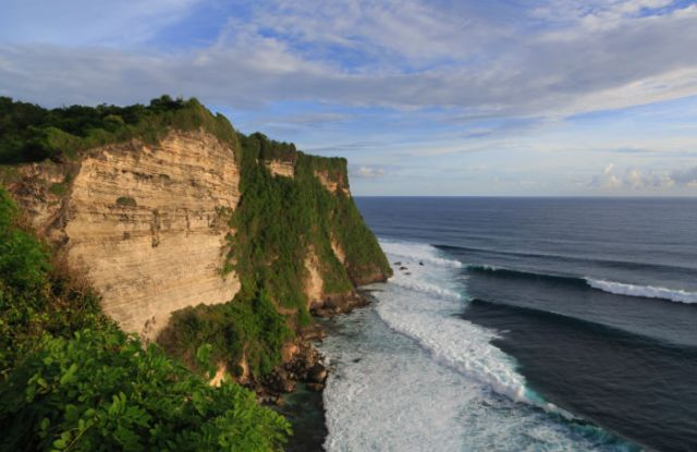 Waves break at the bottom of Uluwatu cliff. The small beach is at the base of the cliffs.
