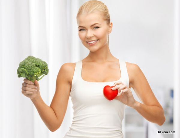 woman holding heart symbol and broccoli