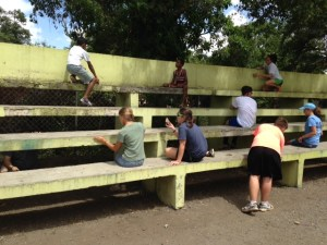 Participants in our mission trip and children from the community work together to scrape and paint bleachers in Santiago.