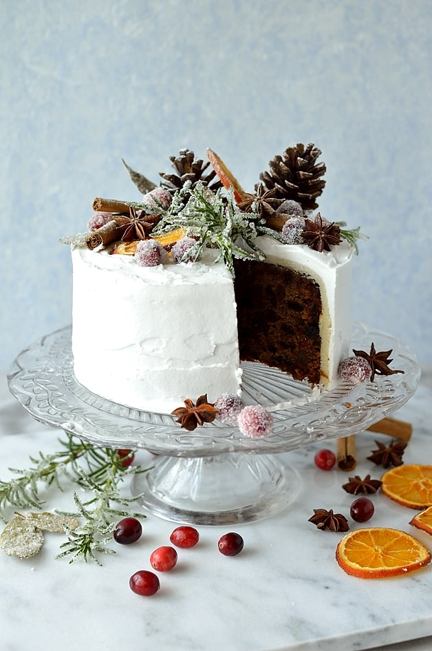 Moist, gingery fruitcake topped with marzipan, royal icing, sugared cranberries, rosemary and bay leaves, dried orange slices, pine cones and whole spices - Domestic Gothess