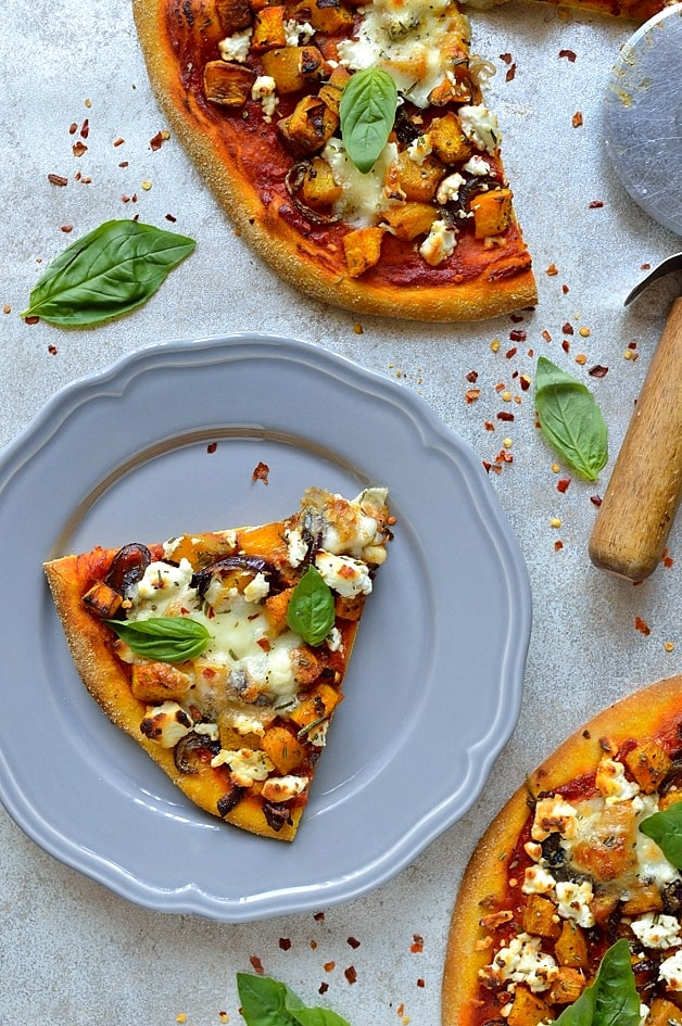 Pumpkin pizza dough topped with roast pumpkin and red onion, tomato sauce, mozzarella, rosemary, goats cheese and basil