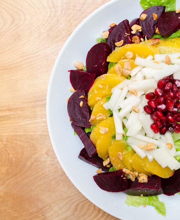 A festive salad with apples, beets, jicama, orange, and pomegranate seeds.