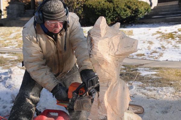 Chainsaw carver works on carved wolf