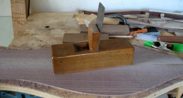Walnut dulcimer back being thicknessed with a toothing plane