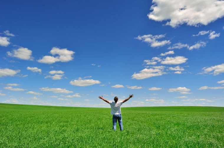 41097334 - man with arms raised on a green field under beautiful sky