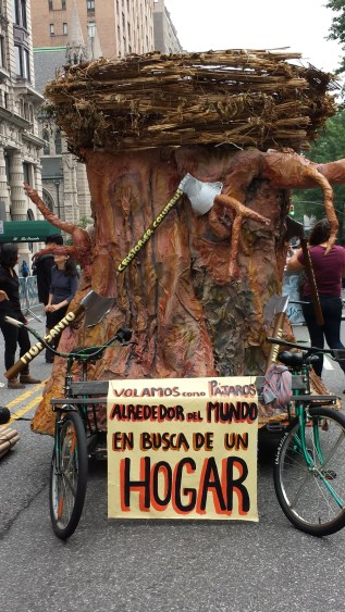 A parade float to be pulled by two bicycles. It is in the shape of a large tree stump with axes sticking out of it and a bird's next on top.