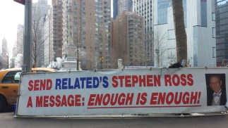 photo of a large banner stretched across a metal frame placed on sidewalk in front of Columbus Circle