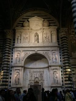 Wall of Michelangelo work in the cathedral in Siena.