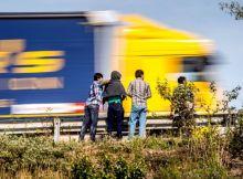 812424-un-camion-passe-devant-des-migrants-au-bord-de-la-route-a-calais-le-5-aout-2015