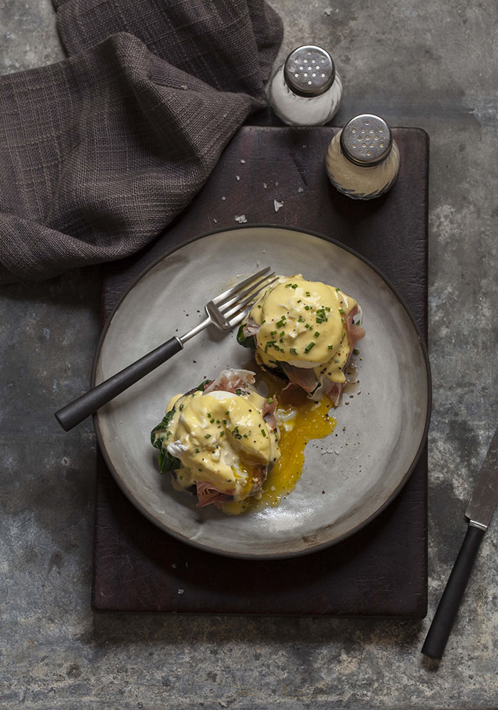 a classic eggs benedict on roasted brown mushrooms
