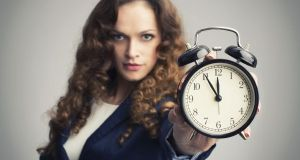 Girl showing alarm clock over gray background