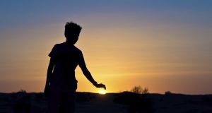 Silhouette of a boy covering the sun with his hand
