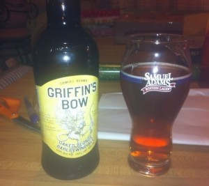 A bottle of Samuel Adams Griffin's Bow next to a Samuel Adams beer glass filled with amber Griffin's Bow