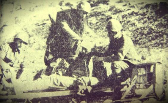 Φωτογραφικό κειμήλιο από τον πόλεμο του 1940 και πιο συγκεκριμένα από το μέτωπο προ του Τεπελενίου. Δεξιά απεικονίζεται ο Βολιώτης Παρασκευάς Μιχαλόπουλος, ο οποίος υπηρέτησε στο 2ο Σύνταγμα Ορεινού Πυροβολικού. Διακρίνεται να εκτελεί χρέη νοσοκόμου και να παρέχει τις πρώτες βοήθειες σε στρατιώτη που τραυματίστηκε στο πόδι