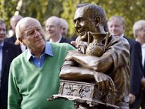 Palmer, in 2005, looking at a statue of himself commemorating the 50th anniversary of his first PGA tour win in 1955 in Toronto