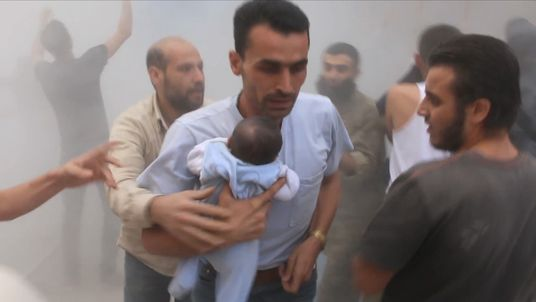 男は離れてアレッポの爆撃エリアから赤ちゃんを運びます