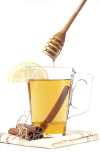 Transparent cup of tea with honey, cinnamon and lemon on white background.