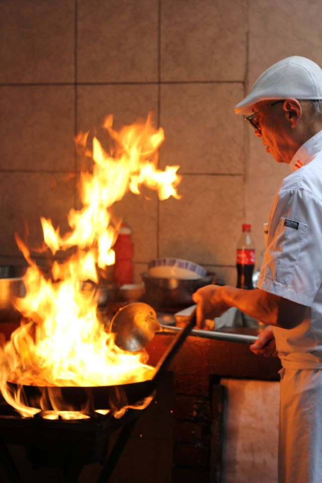Javier cooking over the flames at Chez Wong, Lima