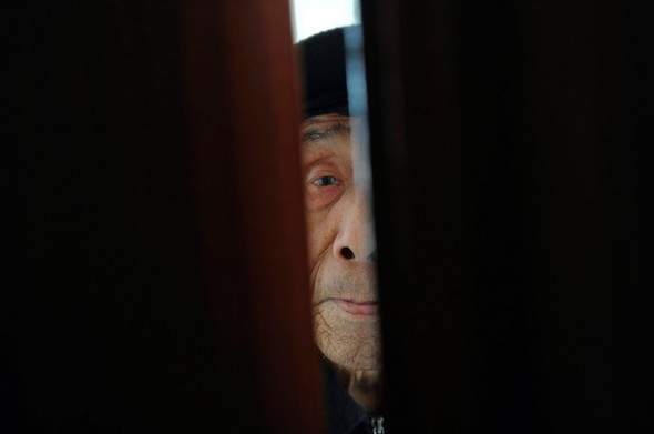 An elderly man peers from a door in a nursing home in Hefei, Anhui province in China.