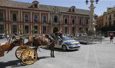 Carroza. Un coche de caballos y una patrulla policial, en la Plaza de la Virgen de los Reyes, que estaban preparadas para la visita de Barack Obama a Sevilla, que finalmente se canceló. /EFE