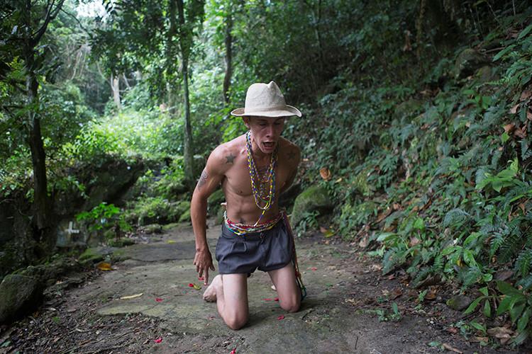 Un hombre camina sobre sus rodillas, a su llegada en el santuario María Lionza en la montaña de Sorte en las afueras de Chivacoa , en el estado de Yaracuy , Venezuela