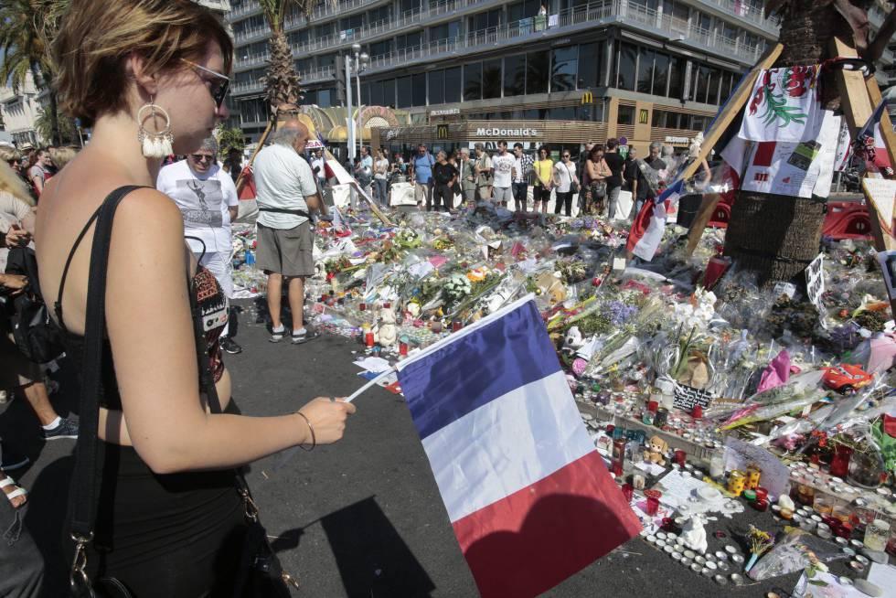 Varias personas observan este lunes el lugar del atentado en Niza, convertido en punto de homenaje a las víctimas.