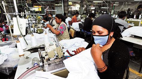 Varios empleados realizan la confección de prendas de vestir en una de las plantas de Enatex.