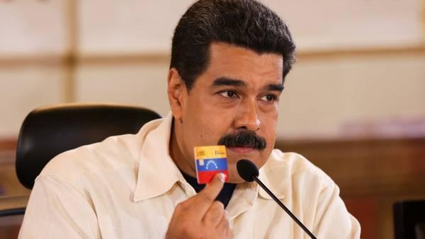 Mensaje. Maduro anunció un aumento de salarios y muestra la tarjeta con la que se puede hacer compras. (EFE)