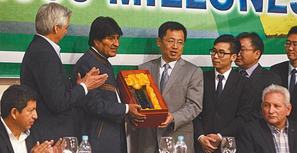 Representantes de las firmas chinas entregan un obsequio al presidente Evo Morales